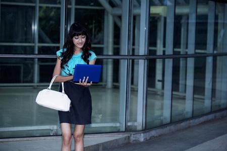 Fashionable asian businesswoman working on laptop photo