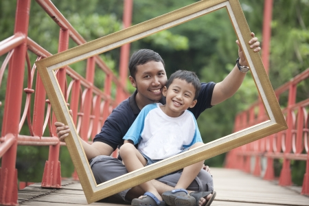 Happy father and son holding a frame on a bridge photo
