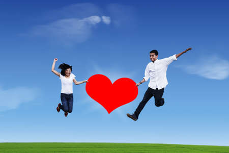Flying couple while holding red heart on blue sky photo