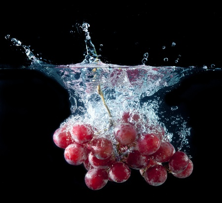 A bunch of fresh grape splashing into water on black