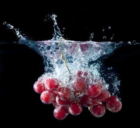 uvas: Un manojo de uvas frescas salpicaduras en el agua en negro