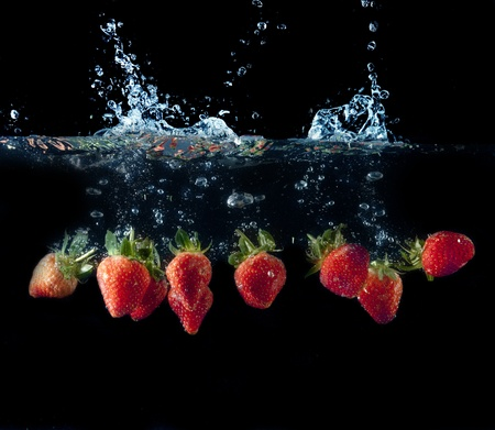 Fresh strawberries splashing in fresh water with water photo