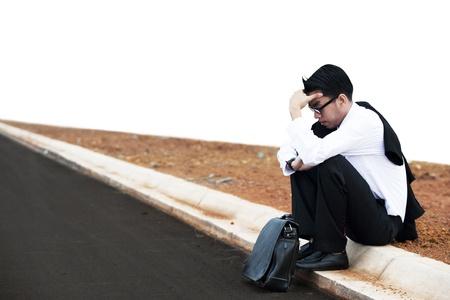 Frustrato uomo d'affari asiatico seduto sulla strada photo
