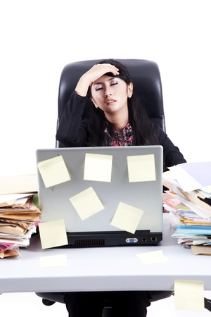 Frustrated businesswoman with stacks of folder, laptop, and postit photo