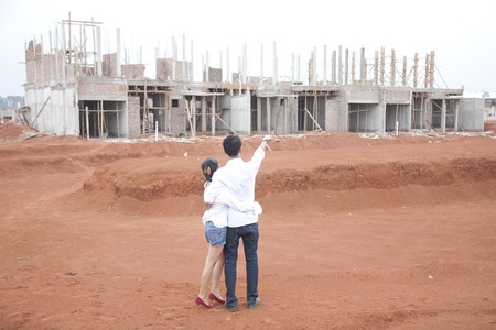 front of house: Young couple looking at their new investment, still under construction