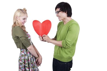 boyfriend: Asian guy gives a caucasian girl a cutout heart shot in studio Stock Photo
