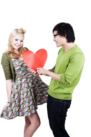 Asian man gives a bug heart cutout to his caucasian girlfriend. Isolated on white photo