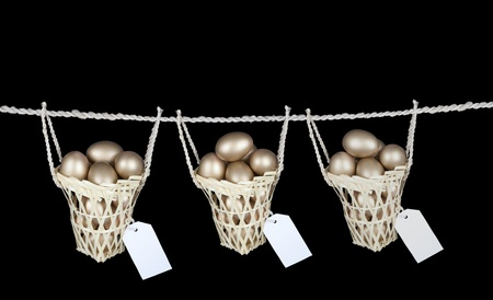 Investment photo concept: golden eggs inside three baskets with copy space isolated over black photo