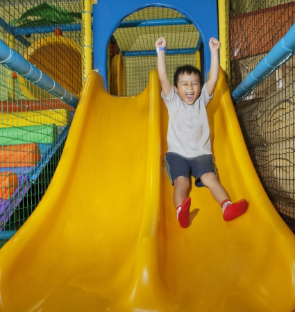 Happy little boy sliding on playground Stock Photo