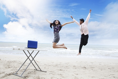 Asian business team jumping on the beach to celebrate their succession photo