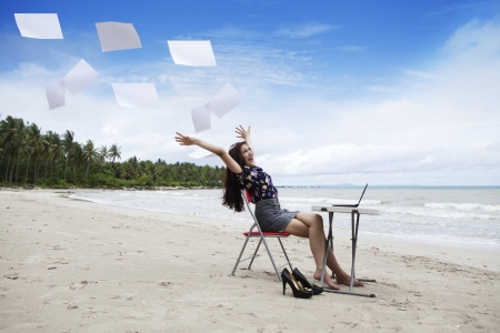 Happy asian businesswoman with working papers on the beach photo