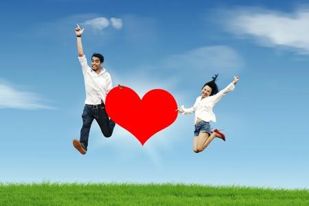 affectionate action: Saltando feliz pareja asi�tica con un recorte de gran coraz�n