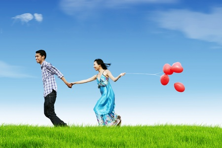 bring: Happy couple running while holding hand and bring red heart balloons Stock Photo