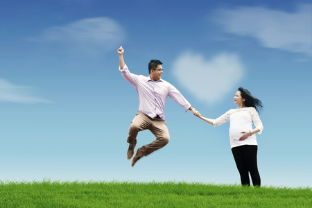 Happy husband with his pregnant wife holding hands in the field Stock Photo - 12150388