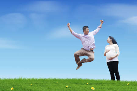A happy young father jumping on the meadow with his pregnant wife  photo