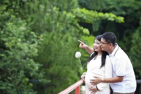 Happy young pregnant couple looking at nature photo