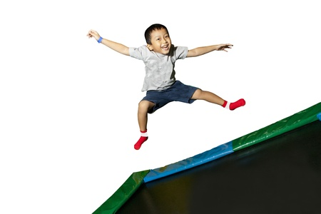 Happy little schoolboy jumping on white background