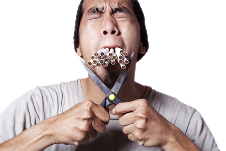 Smoker cutting his cigarette to quit smoking photo