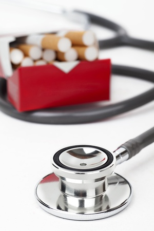 A pack of cigarettes with a stethoscope on white background photo