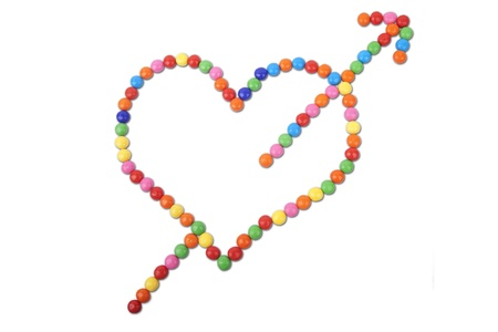 Isolated heart with arrow made of colorful candy photo