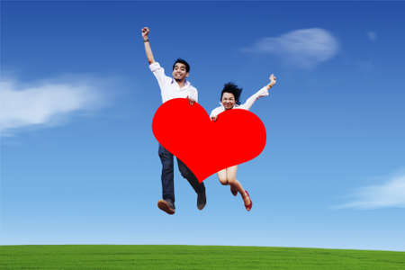 Couple jumping with red heart shape Stock Photo - 12150245
