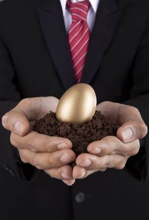 valuable: Investment concept businessman holding a golden egg and soil Stock Photo