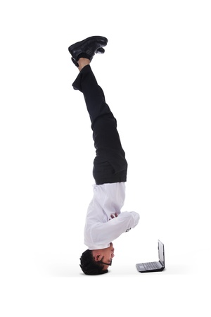 headstand: Isolated businessman headstand with laptop on white background Stock Photo