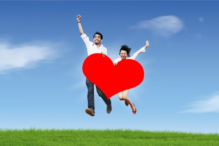 Happy asian couple jumping with a huge heart cutout photo