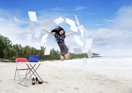 Asian happy businesswoman jumping on the beach photo
