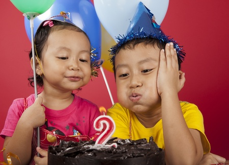 Young asian kids blowing birthday candle photo