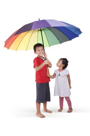 Cheerful children with umbrella on white background photo