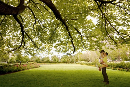 You couple kissing under the green tree Stock Photo - 12150191