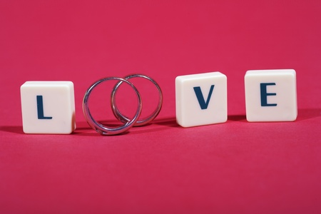 Love concept with wedding rings on red background photo