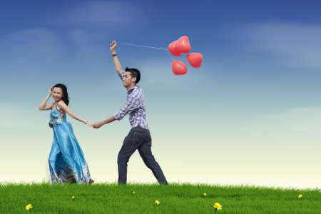palloncino cuore: Happy giovane coppia innamorata con palloncino cuore rosso Archivio Fotografico