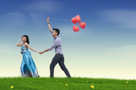 young love: Happy young couple in love with red heart balloon