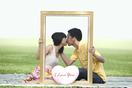 Young lovers kissing in the park with a frame and pink valentine heart shape photo