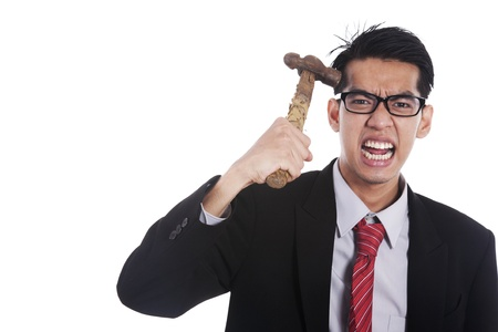 worried executive: Frustrated businessman hitting his head with hammer on white background