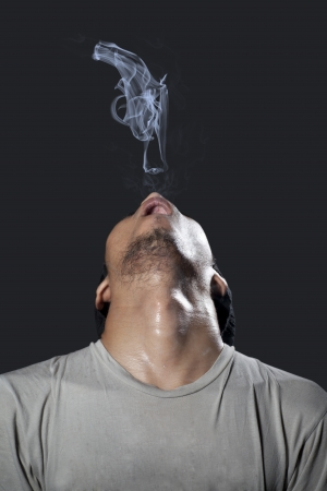 A man with pistol made of smoke on black background photo