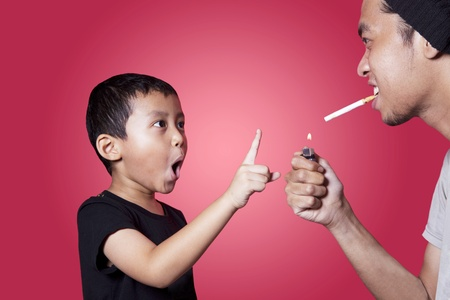 smoking a cigarette: Cute boy give warning to a smoker isolated on red