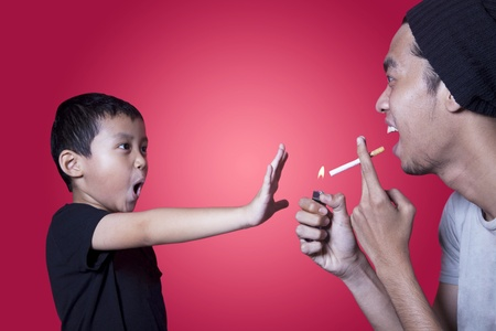 prevent: Boy gives warning to smoker shot in studio isolated on red