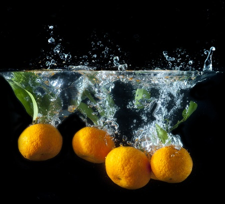 Splashing orange fruit into water on black photo