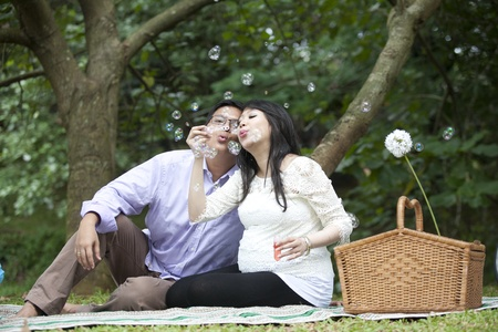 Asian pregnant couple blowing bubbles in the park photo