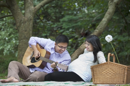 Happy father playing guitar for his unborn baby in the nature photo