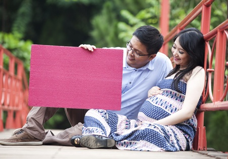 Happy pregnant couple sitting while looking at a red blank board photo