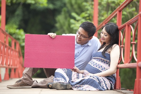 paternal: Happy pregnant couple sitting while looking at a red blank board