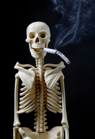 human body substance: Quit smoking concept a human skeleton with cigarette on black background Stock Photo