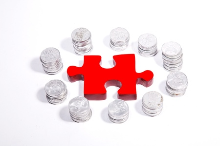 Isolated red puzzle in the center of silver coins circle Stock Photo - 12150270