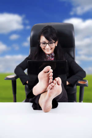 feet crossed: Businesswoman using laptop with Feet Up on a Table  isolated on white Stock Photo