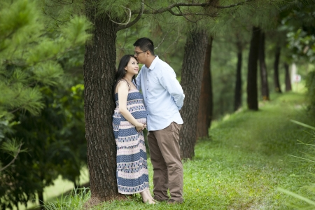 A romantic husband kissing his pregnant wifer under pine tree photo