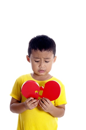 Sad boy holding red puzzle of broken heart photo